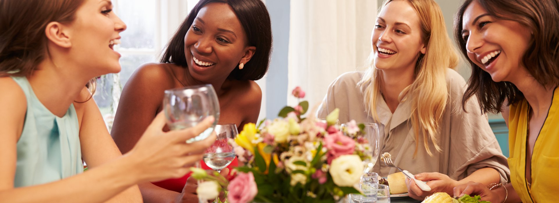 Female Friends At Home Sitting Around Table For Dinner Party